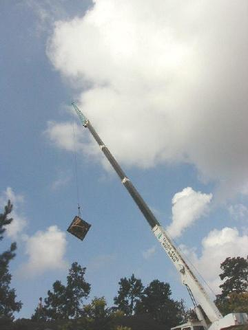 smashed hot tub being craned over house